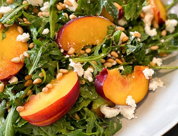 Peach salad topped with pine nuts and feta cheese.