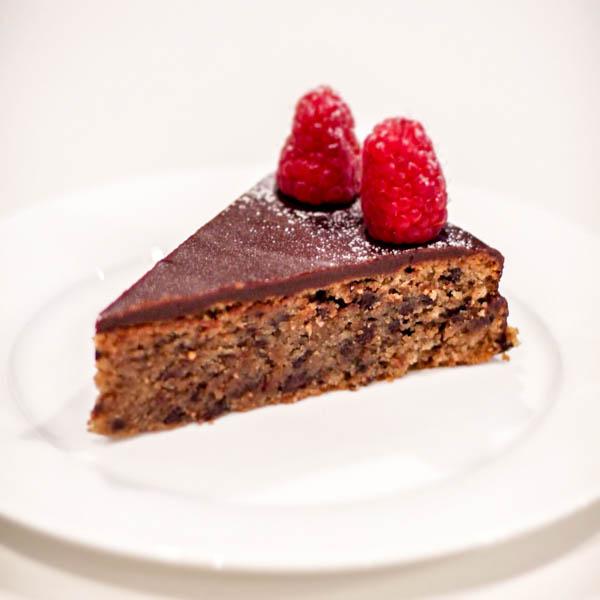 Slice of Chocolate Torta with 2 raspberries on top.