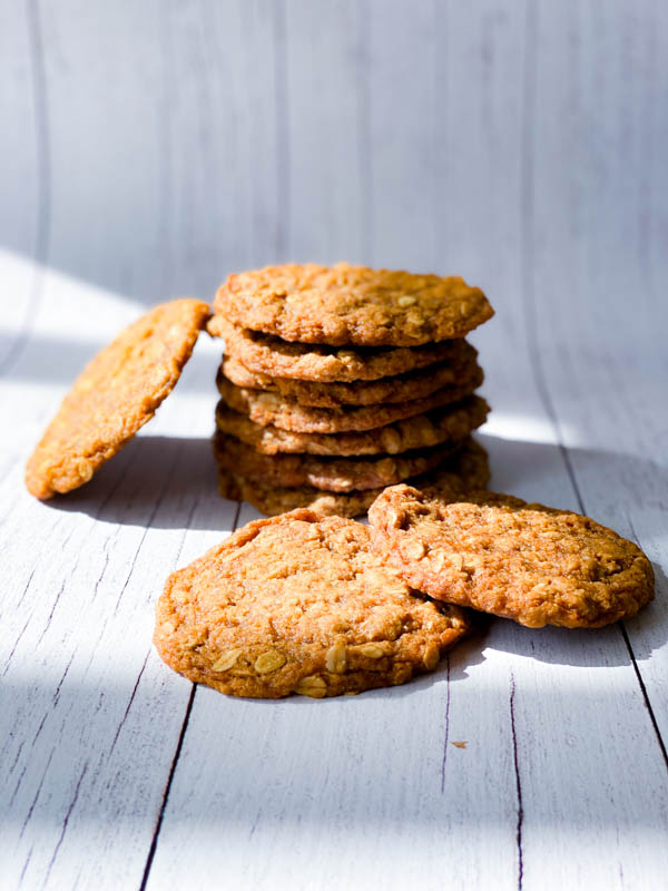 A stack of Anzac Biscuits with a couple in front on white boards.