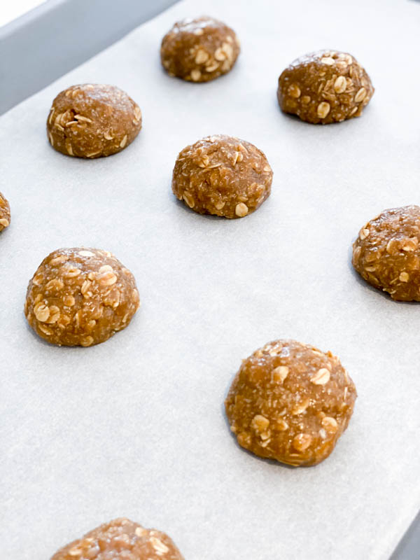 Raw Anzac Biscuit Dough rolled into balls on a baking tray ready for the oven.