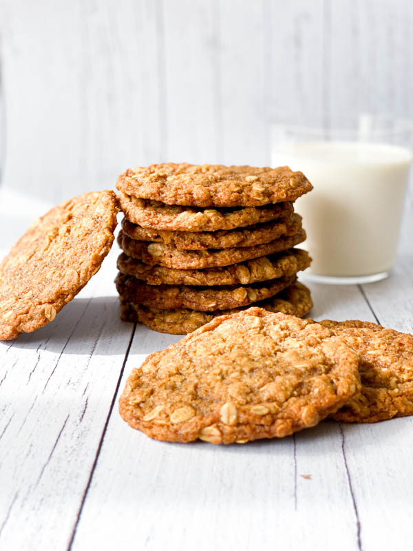 Close up of a stack of Anzac Biscuits with a glass of milk in the background.