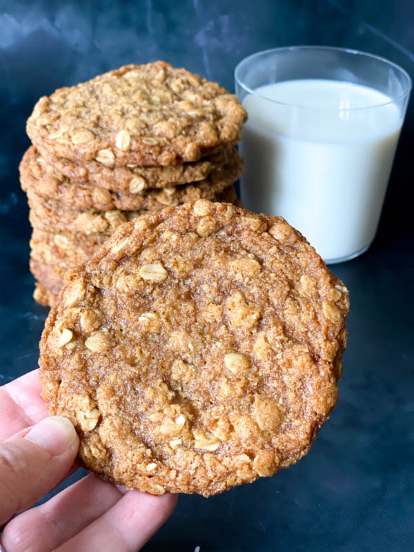 An Anzac Biscuit being held close up with more stacked in the background along with a glass of milk.