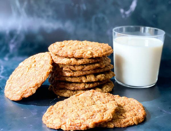 7 Anzac Biscuits stacked in a pile with 2 in front and one to the side with a glass of milk to the right on a lack marble surface.