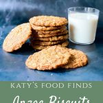 Anzac Biscuits stacked with some in front and one to the side with a glass of milk.