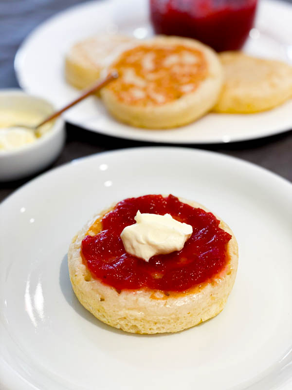 Easy Rhubarb Compote on top of a crumpet with cream on top in the foreground, with more crumpets in the background.
