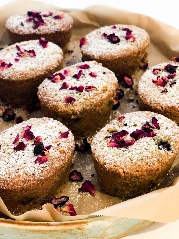 Pistachio Blueberry friands with icing sugar and rose petals on a platter lined with brown baking paper.