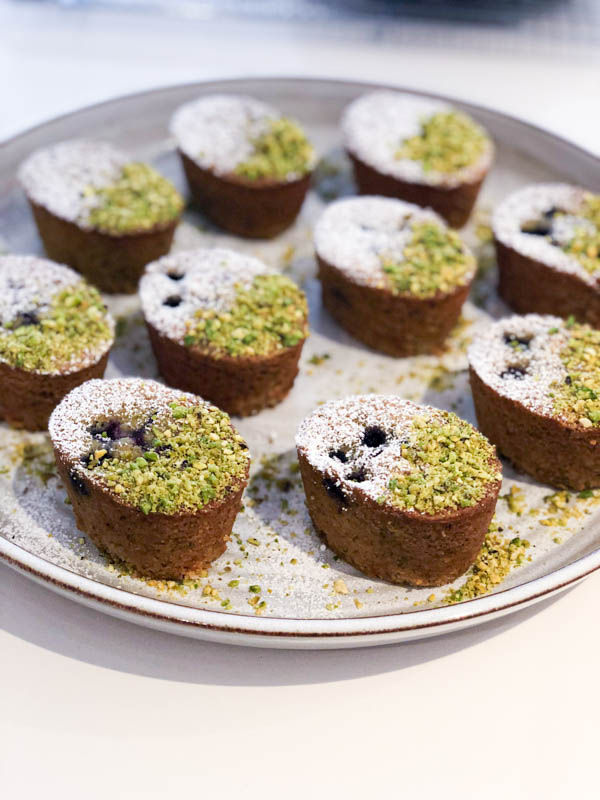 Pistachio Blueberry Friands topped with crushed pistachios and icing sugar on a pottery platter.