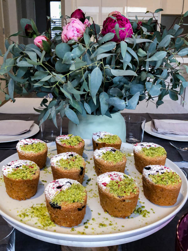 Friands on a white platter in front of a green vase with flowers on a dining table.