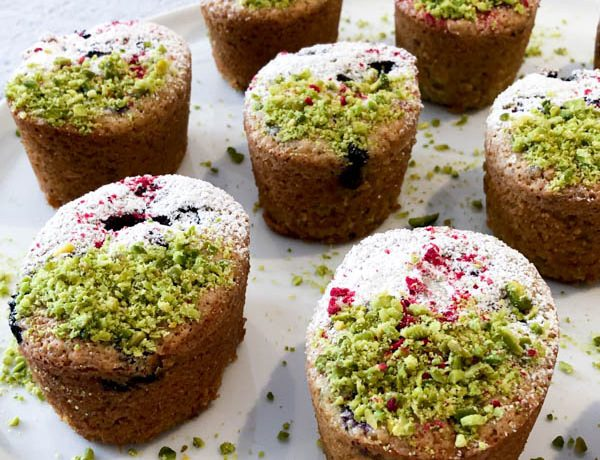 Pistachio Blueberry Friands on a white plate and decorated with Pistachio, Icing Sugar and curshed freeze-dried raspberries.