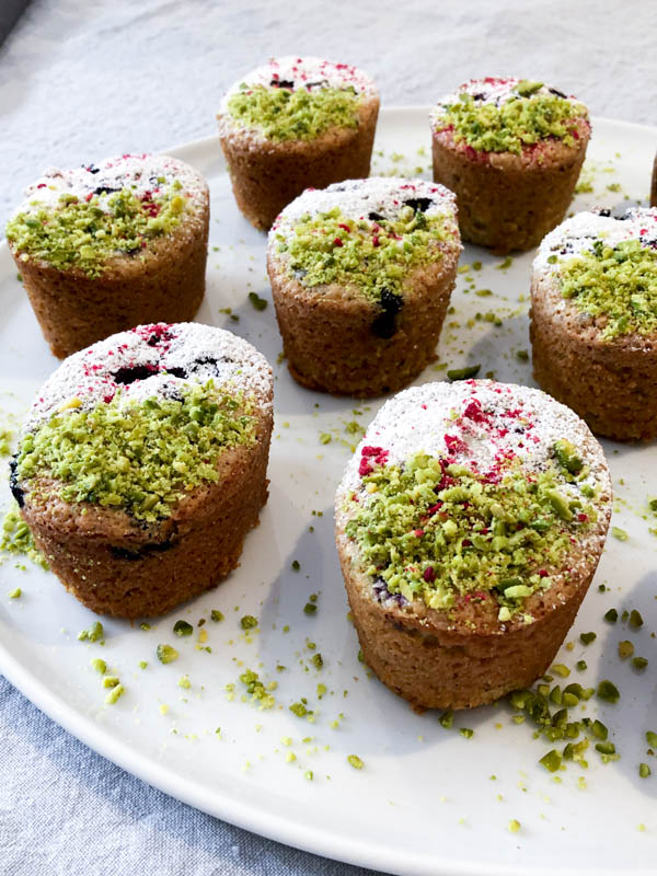 Close up of Pistachio Blueberry Friands decorated with crushed Pistachios on one half and Icing sugar on the other half.