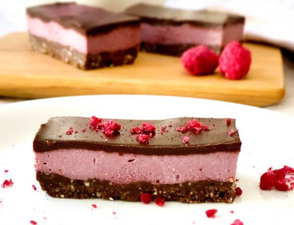 Close up of Raw Raspberry Chocolate Slice with freeze dried raspberries sprinkled around and 2 slices in background.