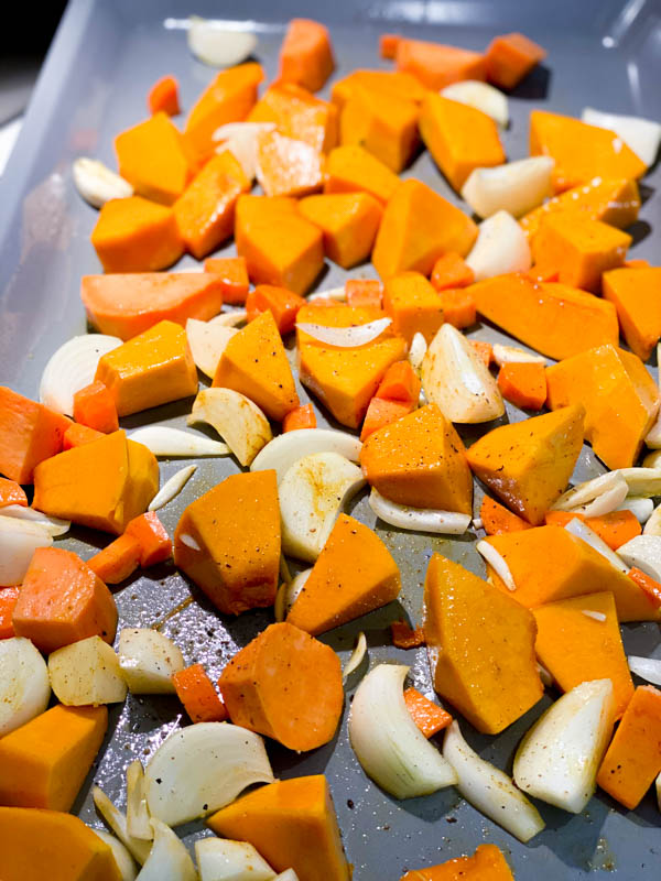 raw pumpkin and potato pieces, carrot, onion and garlic seasoned with salt, pepper, curry powder and olive oil on an oven tray ready to go into the oven.