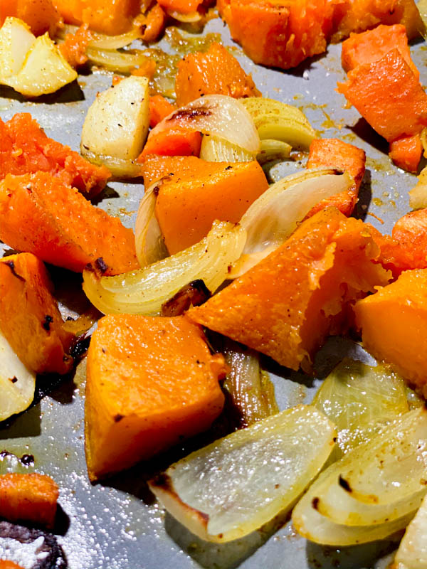 Close up of roasted pumpkin and potato pieces, onion, garlic, carrot and sweet potato roasted on an oven tray, ready to be blended into soup.