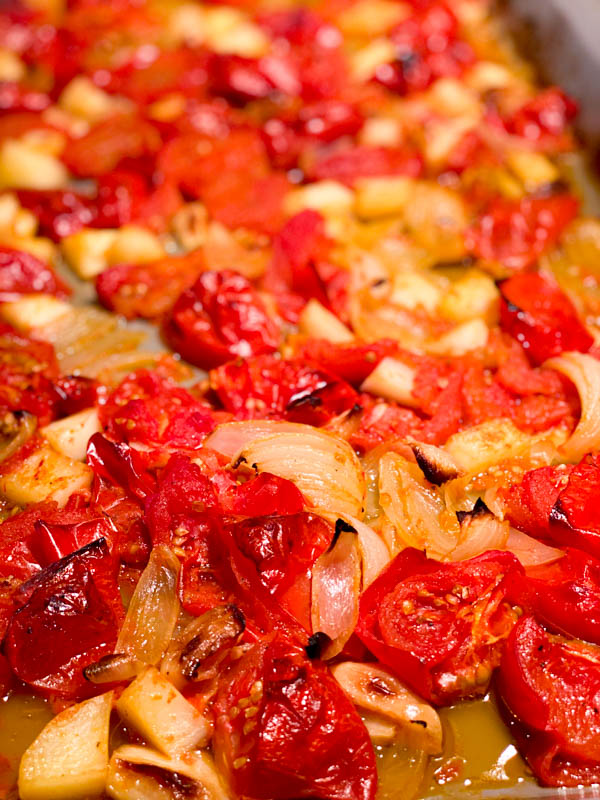 Roasted and caramelised tomatoes, onions and garlic on oven tray.