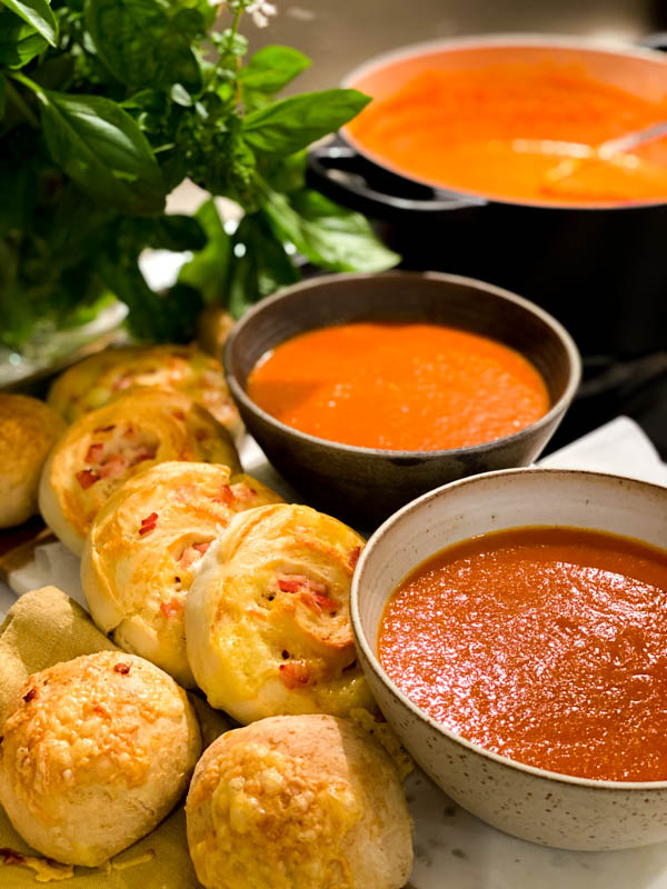 Roasted Tomato Soup in 2 bowls with bread rolls and scrolls ready for serving.