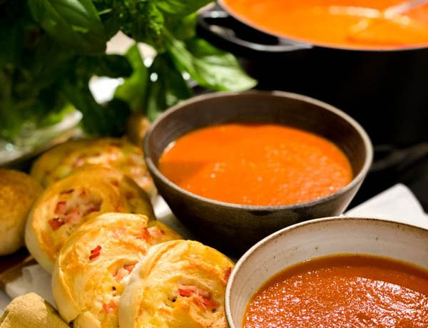 Close up of Roasted Tomato Soup in 2 bowls with Cheese and Bacon Scrolls.