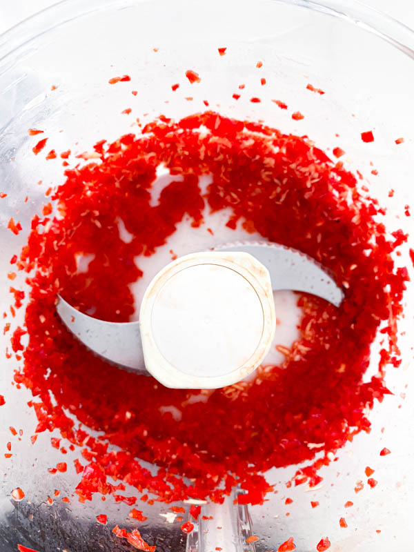 Finely minced red capsicum, chillies and ginger in the bowl of a food processor .