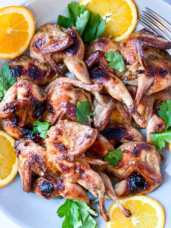 Close up of the Butterflied Quail with orange slices around it and parsley leaves scattered over the top.