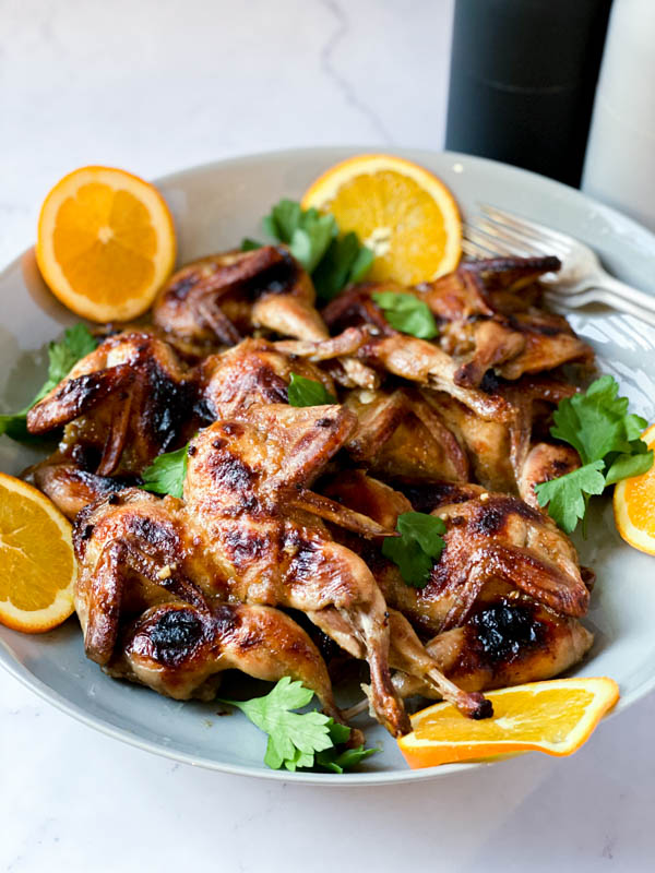 A platter of Butterflied Quail with an Orange, Cumin and Brown Sugar Glaze with orange slices around it.