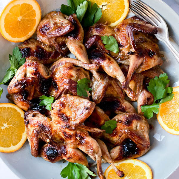 A platter of Butterflied Quail with an Orange, Cumin and Brown Sugar Glaze with orange slices around the outside and parsley leaves scattered over the quail. A couple of forks are on one side of the platter.