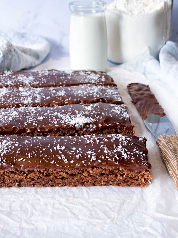Close up of the sliced Chewy Chocolate Coconut Slice with a palette knife beside it and a small jar of milk behind it.