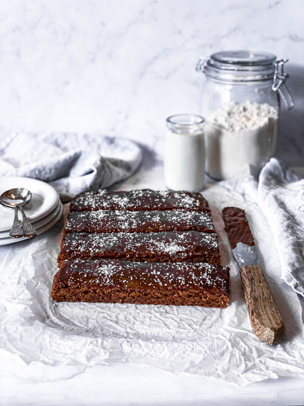The Chewy Chocolate Coconut Slice on a sheet of crumpled white baking paper on a white marble benchtop. A palette knife with chocolate icing is beside it, with plates stacked to the left of it with 2 spoons on top. A large jar of flour and a small jar of milk are behind it.