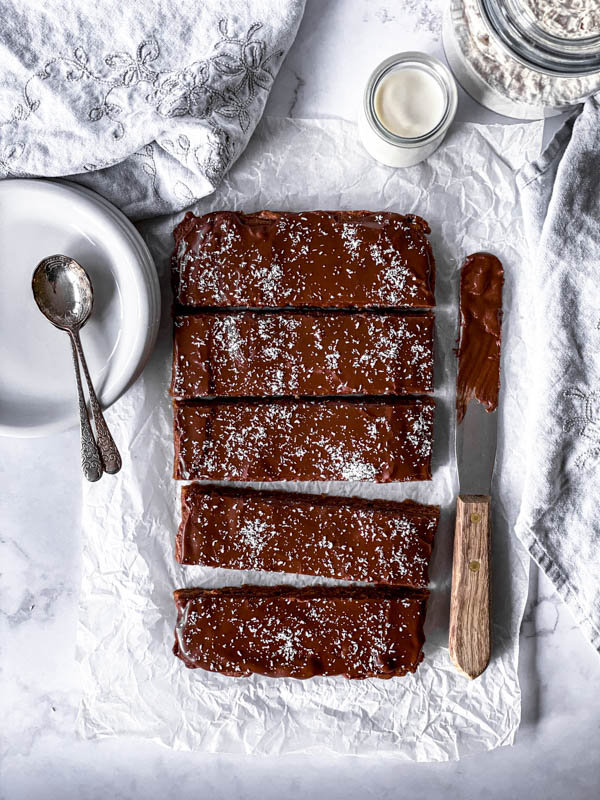 Looking down onto the Chewy Chocolate Coconut Slice with a palette knife to the right and plates and spoons to the left with a jar of milk behind it.