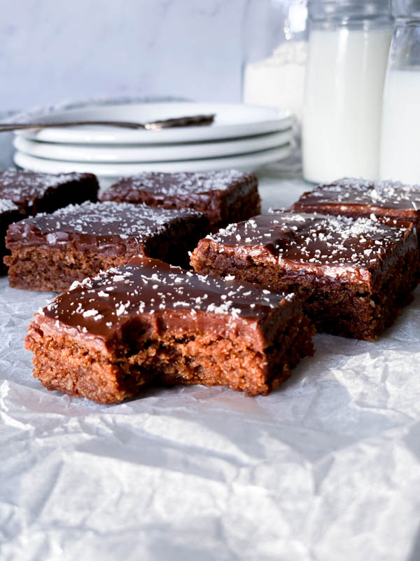 Close up of Chewy Chocolate Coconut Slices in squares with one bitten into at the front. In the background are a stack of 3 plates in the background.