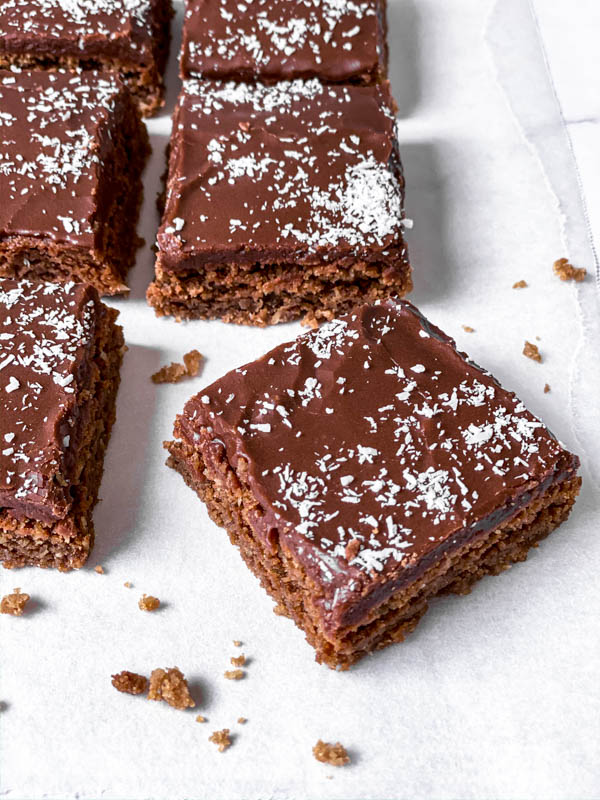 Chewy Chocolate Coconut Slices in squares with a few crumbs around it on white baking paper.