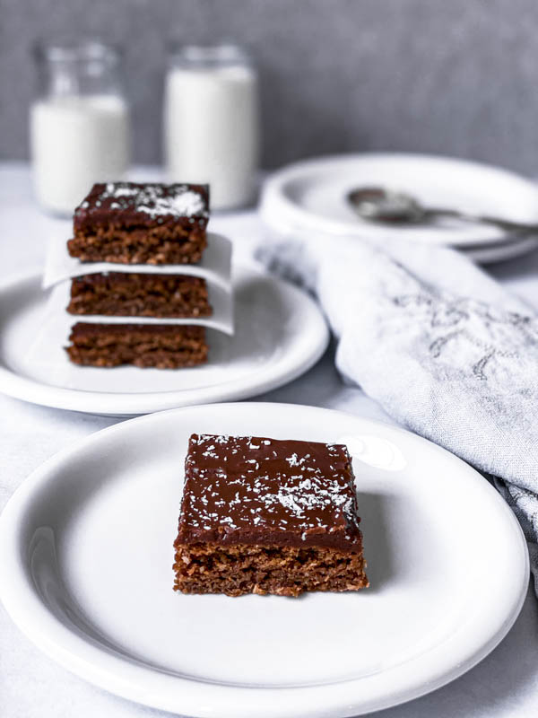 A Chewy Chocolate Coconut Slice piece on a white plate with 3 more pieces stacked on a plate behind it and a napkin beside it.