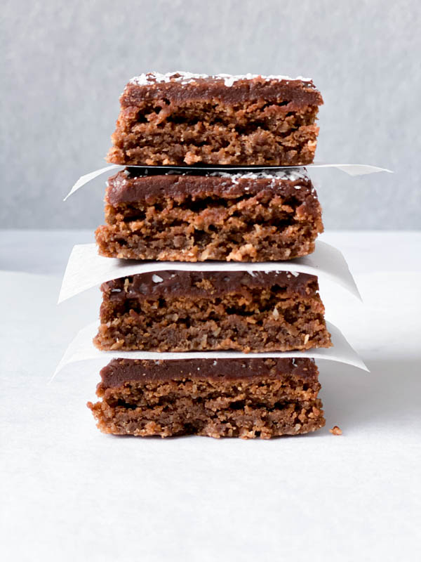 A stack of 4 Chewy Chocolate Coconut Slices with white baking paper in between each slice.