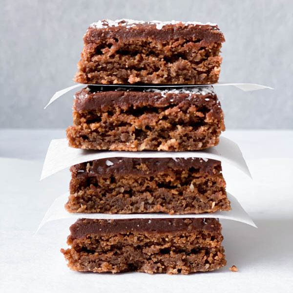 Close up of a stack of 4 Chewy Chocolate Coconut Slices with white baking paper in between.