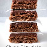 A stack of 4 Chewy Chocolate Coconut Sices with white baking paper in between with a grey background.