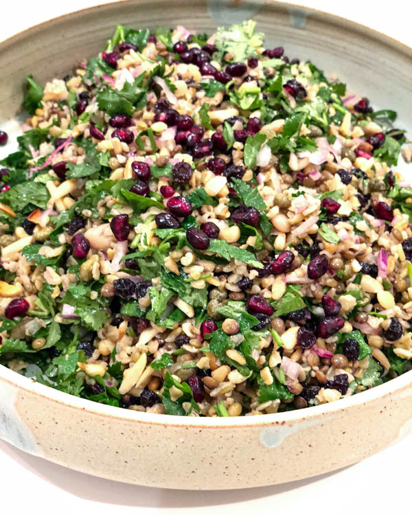The Cypriot Grain Salad on a ceramic platter garnished with pomegranate seeds.