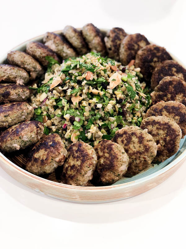 A round platter of Kofte patties with the Cypriot Grain Salad piled in the middle.