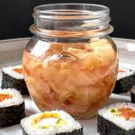 An open jar of Easy Pickled Ginger on a white platter surrounded by pieces of sushi rolls.