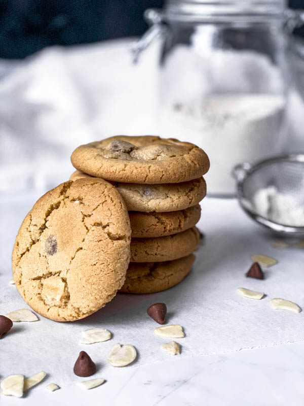 A stack of 5 Gingernut Biscuits with a 6th one leaning against them in the front. Around them scattered on the bench are almond flakes and a few chocolate nibs. In the background are a large jar of flour and a small sieve off to the right side partially out of view.