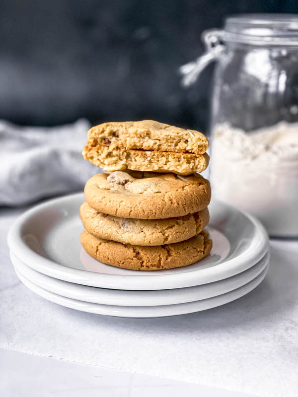 A stack of 3 whole Gingernut Biscuits with a fourth one broken in half on the top. They are stacked on 3 plates with a large jar of flour in the background.