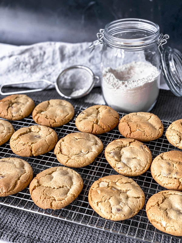 Gingernut Biscuits in 3 rows cooling on a wire cake resting rack with a jar of flour and a small sieve in the background. Everything is set on a dark grey tablecloth.