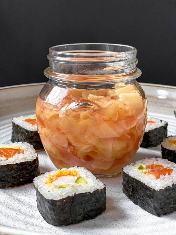 Looking front on at a jar of Easy Pickled Ginger with the lid off. It is in the middle of a large white pottery platter and has sushi rolls all around the jar.