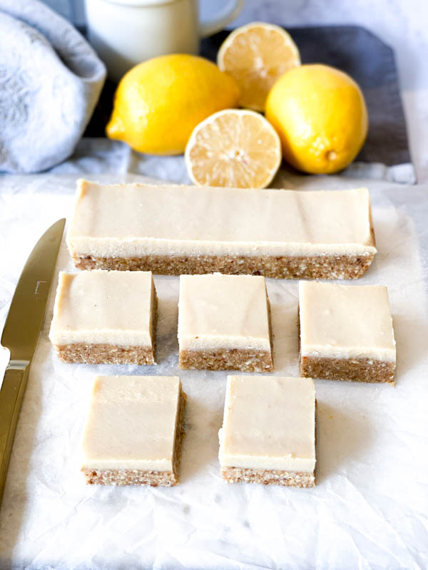 Top view of Raw Lemon Slice with lemons, napkins and a white coffee cup in the background and a gold knife to the left of the slices.