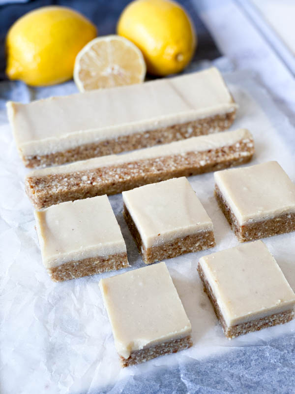 Side front view of Raw Lemon Slice on baking paper with lemons in the background.