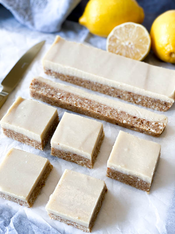 Close up of Raw Lemon Slice cut into squares with lemons in the background.