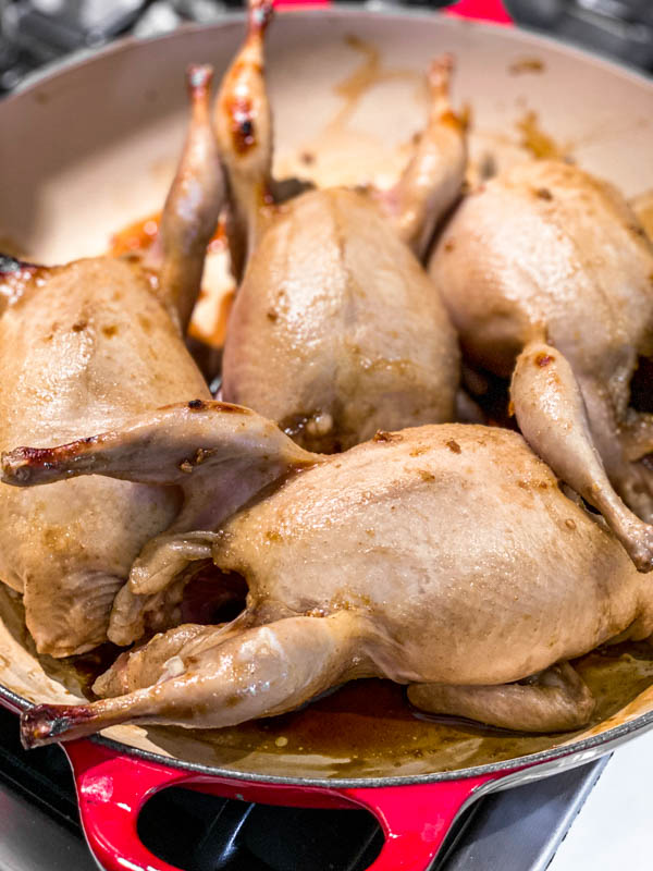 The marinated Roasted Pomegranate Quail in a pan, ready to go into the oven