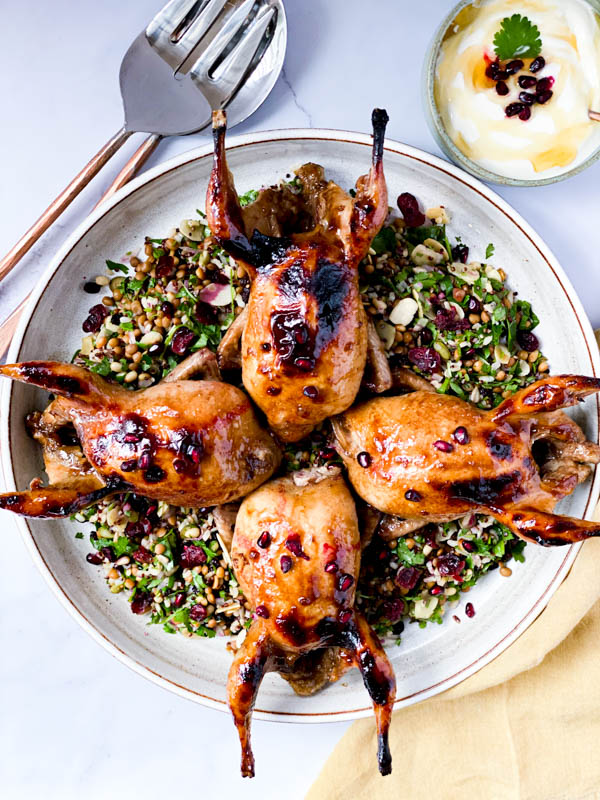 Looking down onto the round white platter with 4 Roasted Pomegranate Quail on top of a Grain and Herb Salad. Around the platter is a set of salad servers, a bowl of honey yoghurt and a mustard coloured napkin.