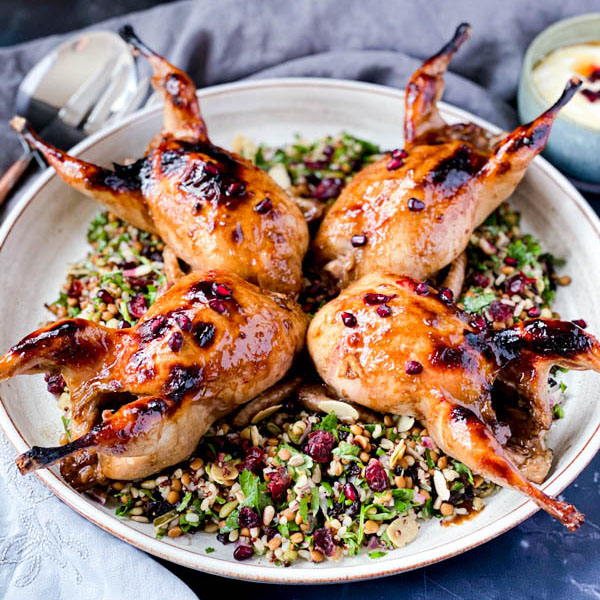 The 4 Roasted Pomegranate Quails sitting on a Grain and Herb Salad on a large white ceramic platter. It is surrounded by salad servers, grey napkins and a bowl of yoghurt dressing.