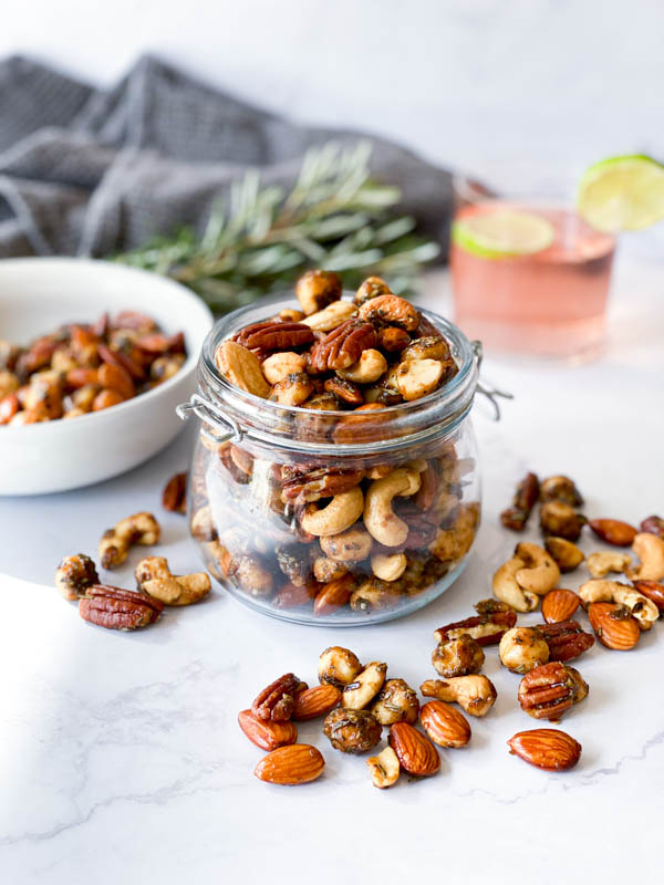 A jar of Sweet and Spicy Nuts in the centre without a lid on a white marble bench. Nuts are on the bench around it as well as in a white bowl to the left. Also in the background are a napkin, glass of gin and sprigs of rosemary.