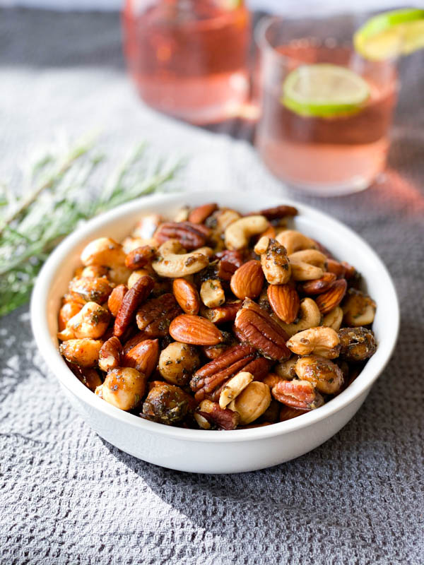 A white bowl of Sweet and Spicy Nuts in the centre on a grey tablecloth with sprigs of rosemary beside it and 2 glasses of gin in the background.