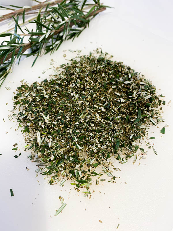 Finely chopped rosemary with a sprig in the background on a white bench.