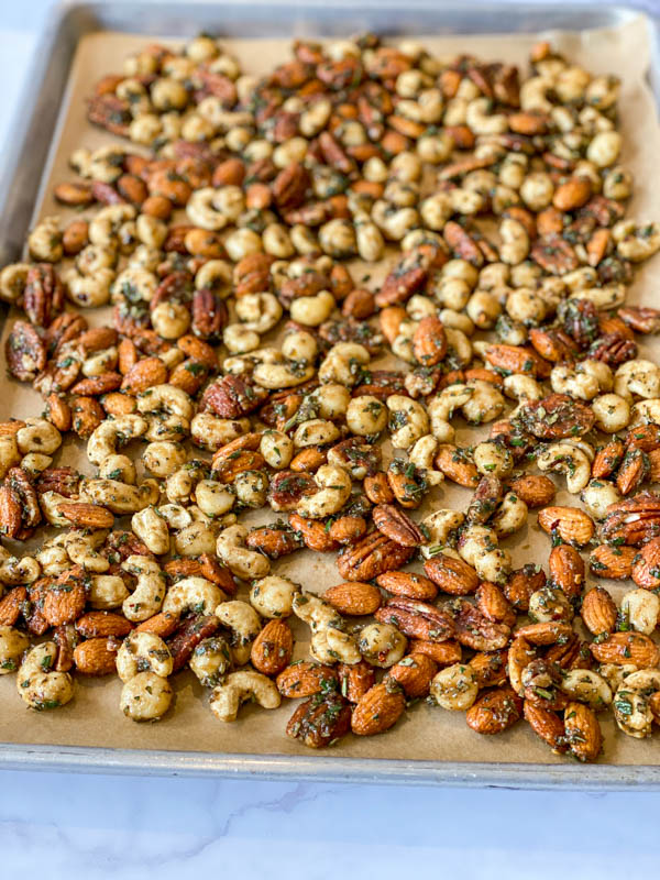 Sweet and Spicy Nuts spread out on a baking tray lined with brown baking paper, ready to be cooked.